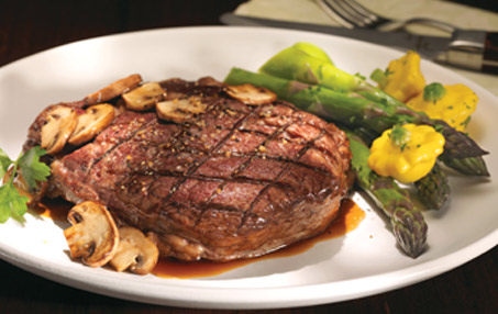 Plate of grilled steak covered with mushroom sauce, served with asparagus and yellow summer squash