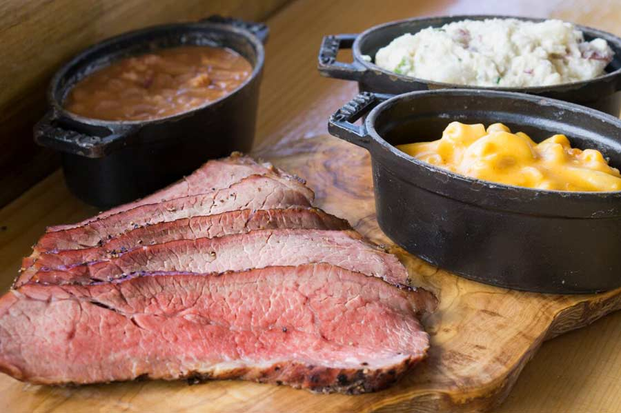 Sliced tri-tip on wood block with baked beans, macaroni and cheese and potato salad