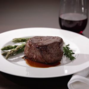 Filet with asparagus and rosemary spring. Glass of red wine.