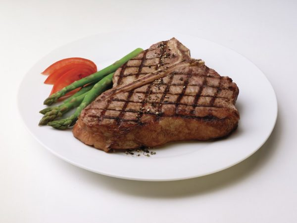 Grilled Porterhouse Steak on plate with asparagus and tomato garnish