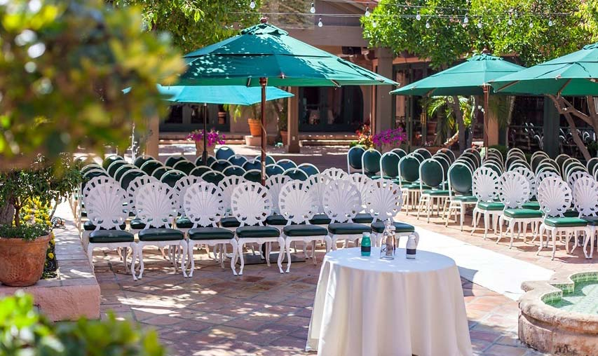 Outdoor courtyard with green umbrellas set for wedding ceremony at Harris Ranch