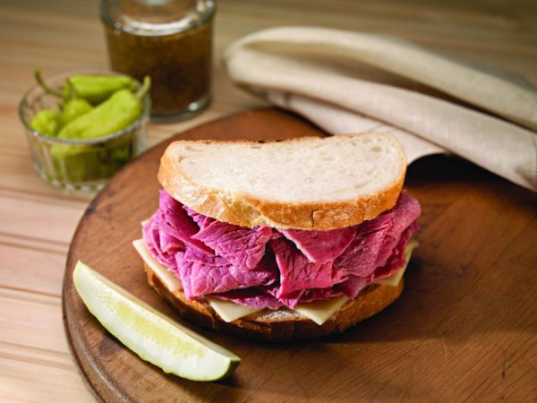 Corned beef sandwich on round board with pickle spear