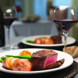 Table for two with matching entrees of filet, roasted potatoes, asparagus and red wine