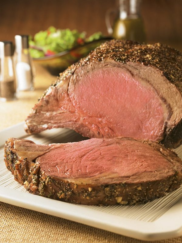 Prime rib on platter with mixed salad in background