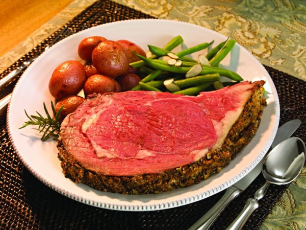 Prime rib sliced on plate with roasted potatoes and green beans almandine