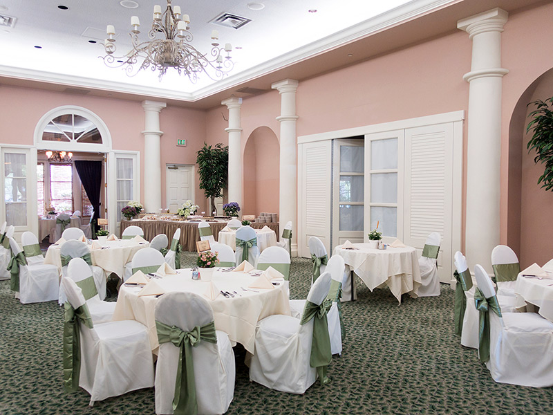 Garden Ballroom set with chairs covered in white drapes and tied with sage-green sash