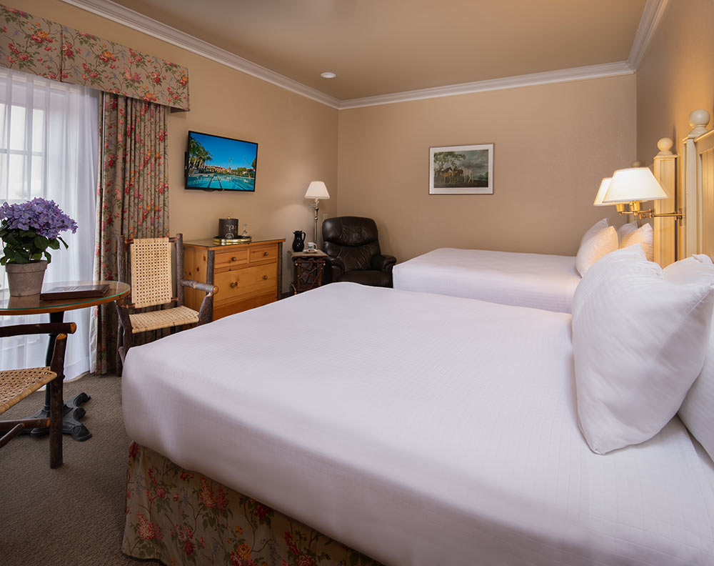 Deluxe Double Queen guest room at the Harris Ranch Inn. Scene shows access to patio