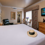 Deluxe king guest room at the Harris Ranch Inn. Straw hat with Harris Ranch logo on foot of bed