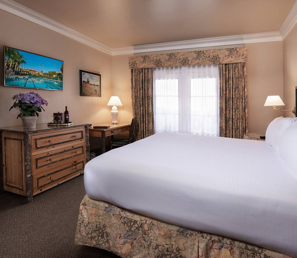 Executive Suite at the Harris Ranch Inn. Bedroom with crisp white bedding, large floor-to-ceiling window on back wall