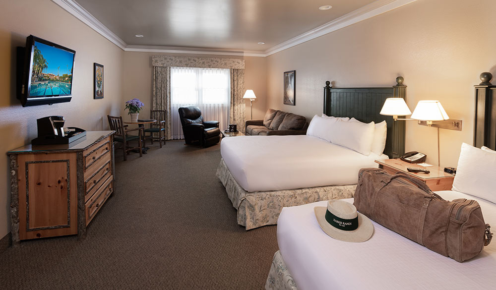 Family Suite at the Harris Ranch Inn. Large room with two beds, seating area and a small round table with two chairs