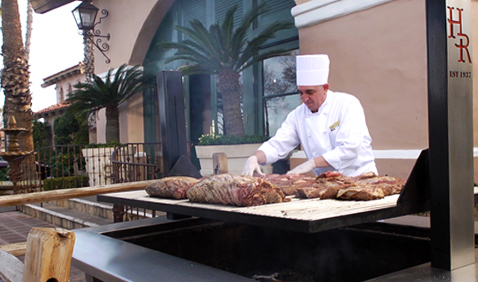 Chef at outdoor BBQ at Harris Ranch. Preparing steaks for the grill