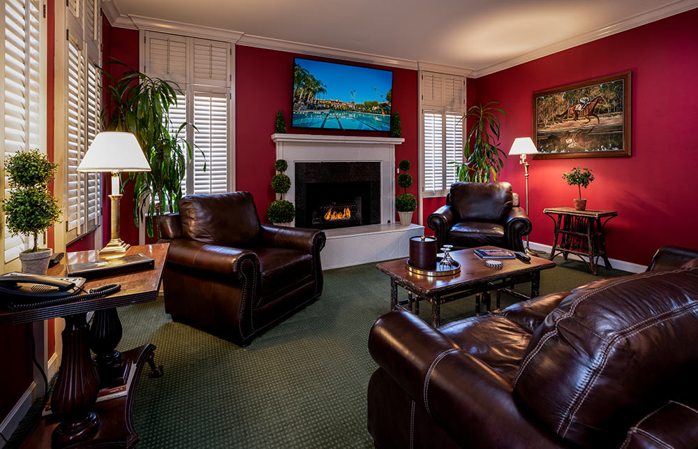 Living room in Presidential Suite. Lit fireplace, large leather sofa and two chairs in deep, rich brown