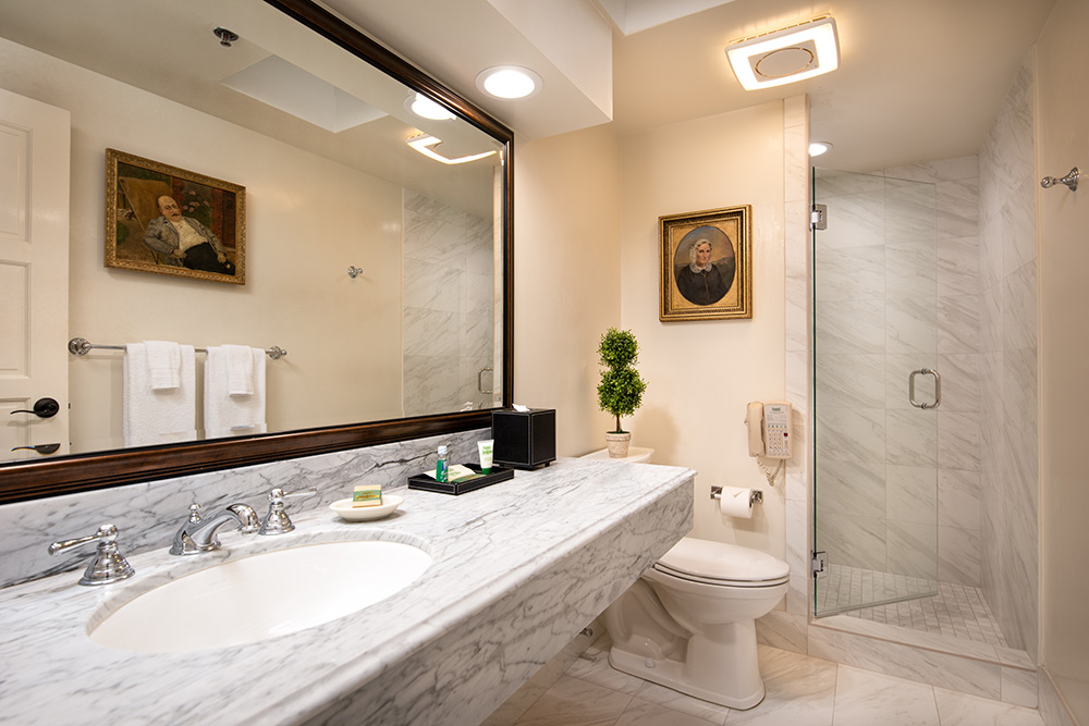 Elegant bathroom in Presidential Suite at the Inn. Marble countertop and shower with glass door