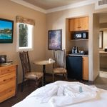 Triple Crown King Guest Room. Bathrobe at foot of bed, bistro table with two chairs, small fridge, coffee maker and microwave