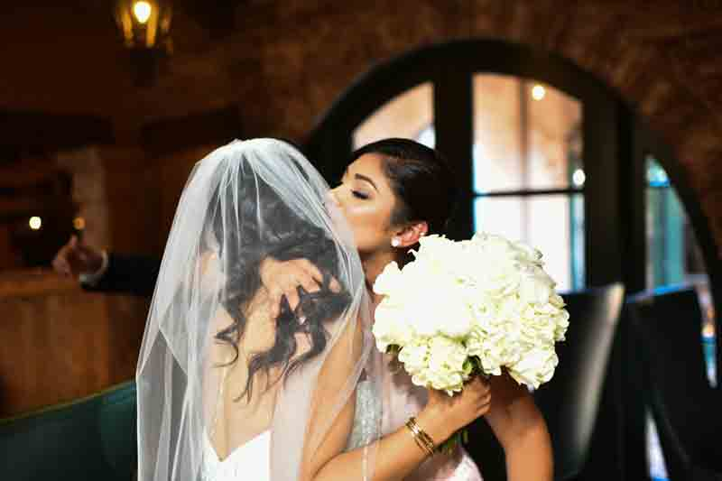 Veiled bride holding white bouquet, embraced my member of bridal party
