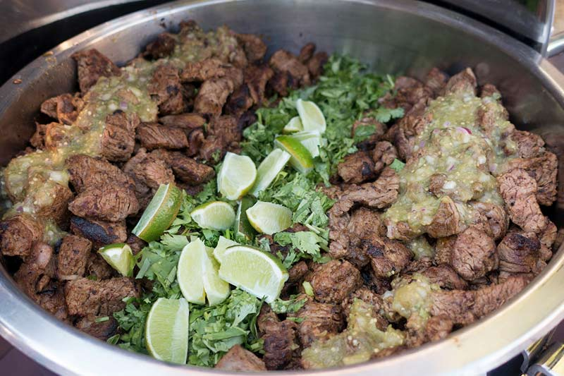 Beef entree in buffet serving presentation. Fresh lime and cilantro garnish