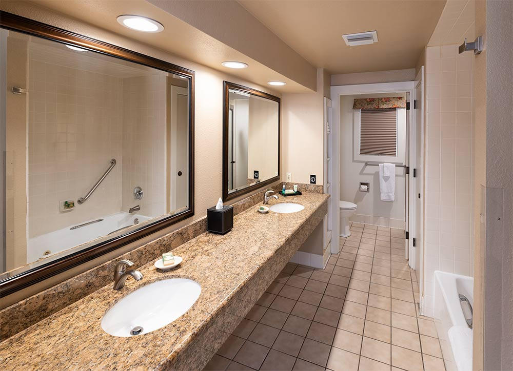 Bathroom in the Luxury Suite. Double vanity with large mirrors and tile floor