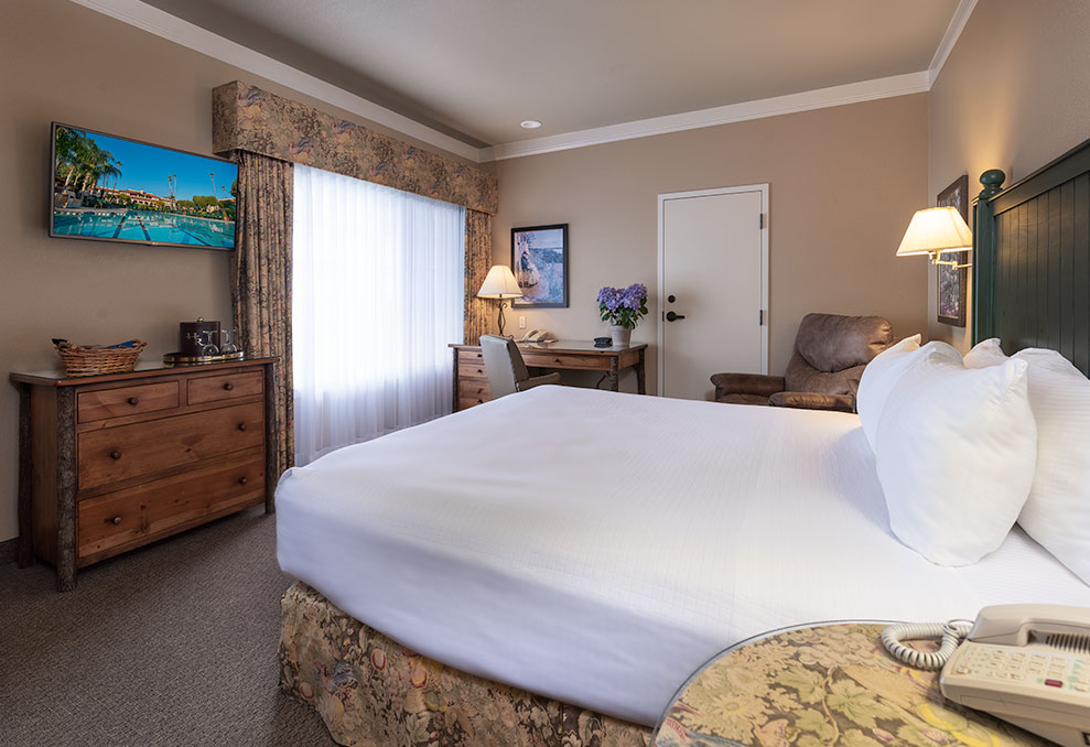 Triple Crown King room at Harris Ranch Inn. Large window, leather chair and crisp white bedding