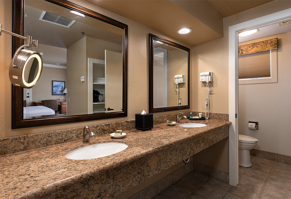 Bathroom in the Triple Crown King Guest Room. Double vanity with large mirrors and wall-mounted hair dryer