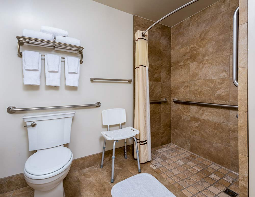 Accessible bathroom at the Harris Ranch Inn, shows toilet with mounted bars, shower chair, and walk-in shower with curtain and bars.