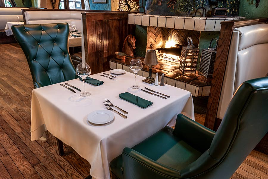 Table for two alongside fireplace at the Harris Ranch Steakhouse Restaurant. Rich hunter-green leather chairs, white table cloth
