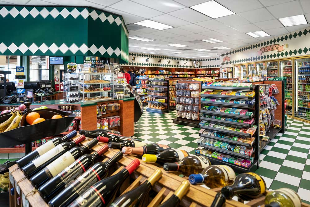 Fast Track Convenience Store. Wine rack in foreground, food aisles in background, beer & wine refrigerated case on back wall