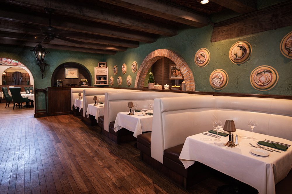 Harris Ranch Steakhouse dining area. Dark wood floor, four cream-colored booths, white tablecloths
