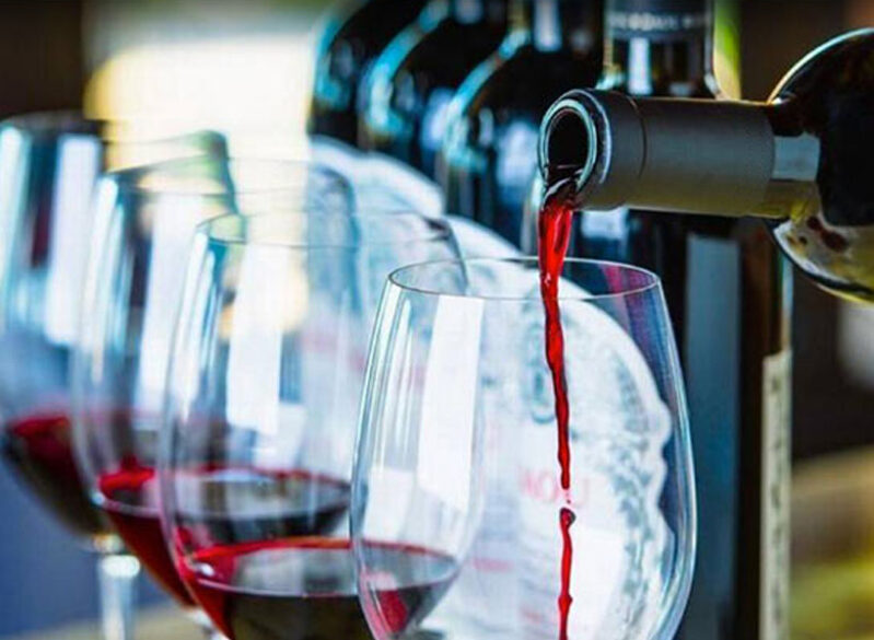 Row of wine glasses being filled with red wine from bottle