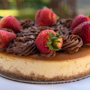 New York Style Cheesecake topped with fresh, whole strawberries