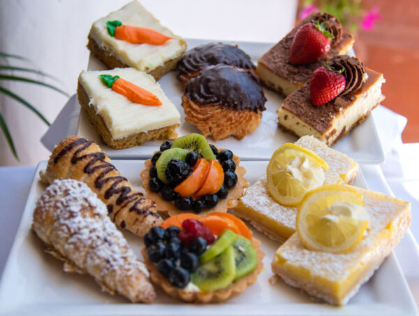 Variety of pastries available in the pastry box, includes carrot squares, chocolate macaroons, cheesecake squares, cream-filled horns, assorted fruit tarts and lemon bars. Two of each for a dozen pastries